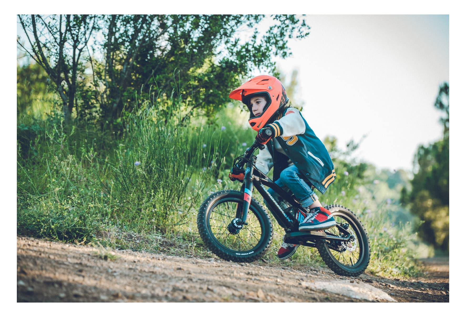 enfant avec un casque orange sur le mini vélo électrique Mondraker Grommy 16 noir et bleu